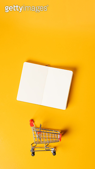 content marketing concept,top view oepn book with shopping cart on yellow desk surface.leave space for display your content.vertical background 9-16 ratio for advertise on mobile media