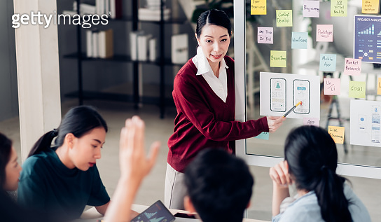 ux developer and ui designer hand up asking question boss about mobile app interface design on whiteboard in meeting at modern office.Creative digital development mobile app agency