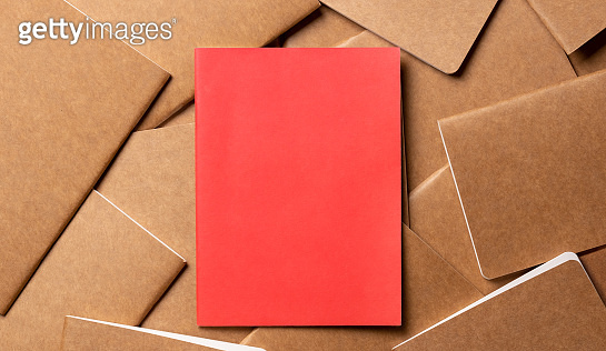 red notebook on brown kraft notebook disorder alignment on table background.mockup template for display content or design.content marketing concept