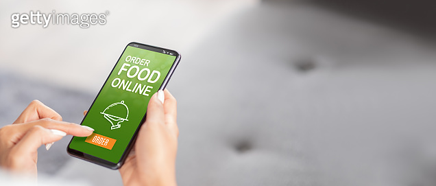 close up woman hand order food online on mobile app at home.online purchase store.online shopping omni channel concept