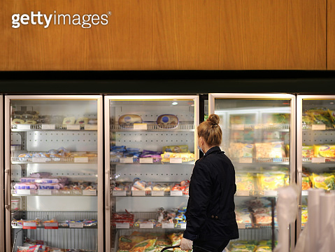 supermarket shopping, face mask and gloves,Woman choosing frozen food from a supermarket freezer