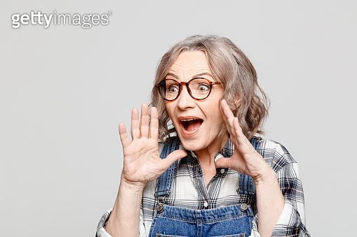 Portrait of suprised senior woman wearing checkered shirt