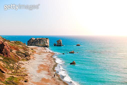Seashore and pebble beach with wild coastline in Cyprus island, Greece by Petra tou Romiou sea rocks, panorama