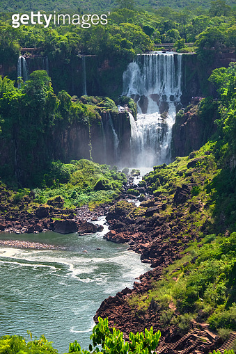 Iguazu waterfalls in Argentina, view from Devil's Mouth. Panoramic view of many majestic powerful water cascades creating mist. Panoramic image of Iguazu valley with lush subtropical forest.