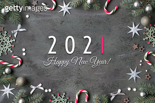 Happy New Year 2021 text. Flat lay with fir twigs decorated in green, pink and silver