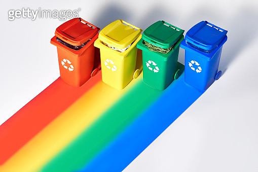 Four color coded recycle bins, isometric projection on geometric rainbow paper background with copy-space. Recycling sign on the bins - red, blue, yellow, green. Waste separation concept background.