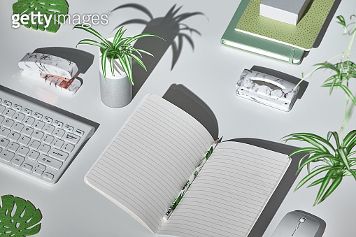 Concept trendy background with modern office supplies in white, mint green and marble. Isometric projection, geometric layout with monstera leaves. Notebook, stapler, keyboard, mouse, stapler.