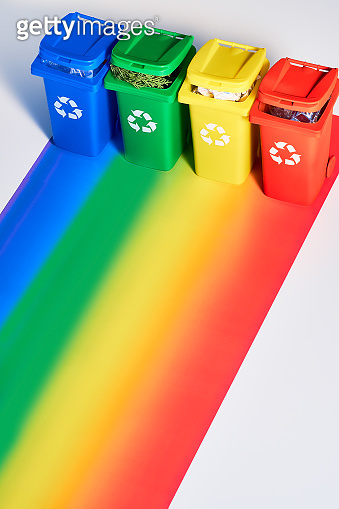 Four color coded recycle bins, isometric projection on geometric rainbow paper background with copy-space. Recycling sign on the bins - red, blue, yellow and green.