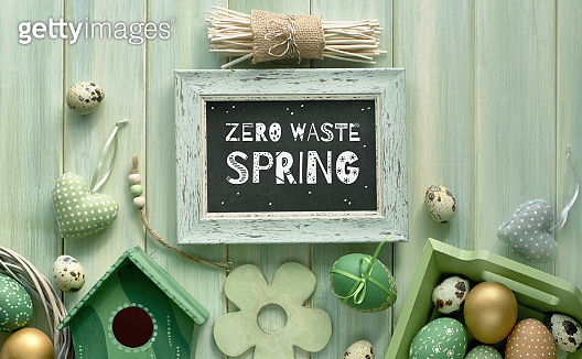 Easter flat lay on light green wooden planks with springtime decorations and blackboard with text