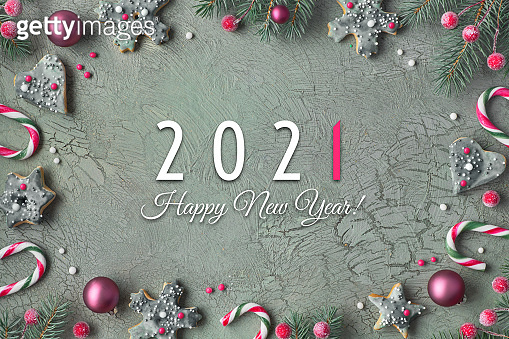 Happy New Year 2021 text. Flat lay with cookies, fir twigs decorated with red, green natural toys