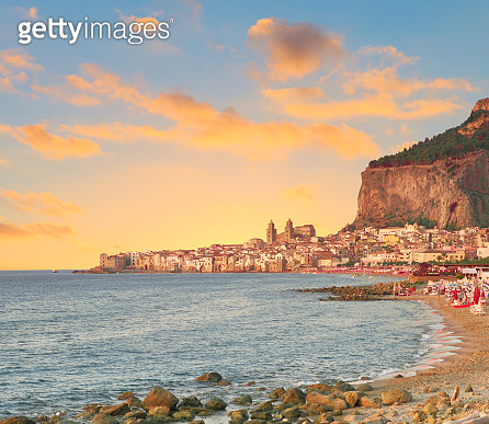 Glorious golden sunset over Cefalu, a town near Palermo, located on Tyrrhenian coast of Sicily, Italy. Cefalu is popular travel destination in Europe, for summer beach vacations