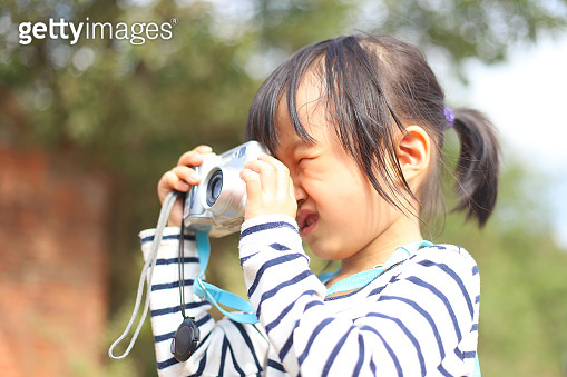 a Asian girl taking photos with a digital camera.