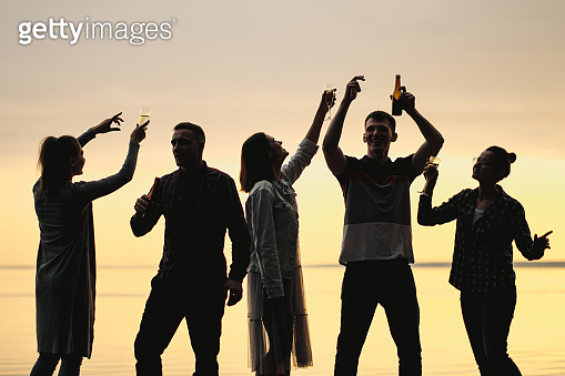 Friends party on beach at sunset. Women and men have fun, drink beer and wine, dance and laugh.