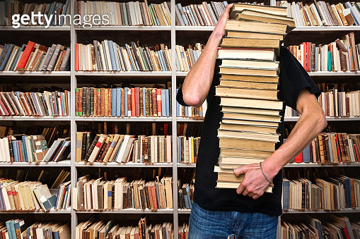 A young man holds a stack of books