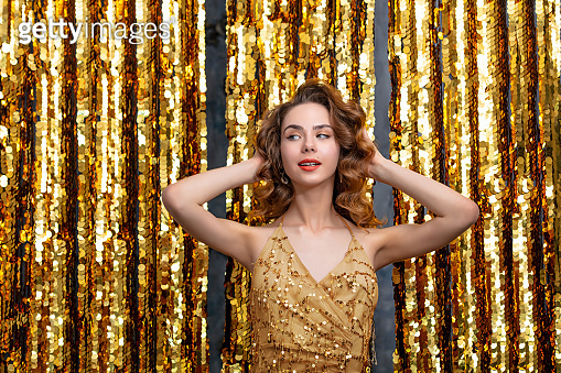 Beautiful young girl model at a party in a gold dress on a gold background