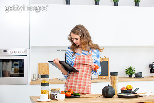 Beautiful and cute young girl at home in the kitchen with a tablet in her hands