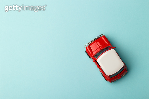 Red small toy car on pastel background