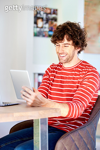 Happy young man using touchpad while working from home