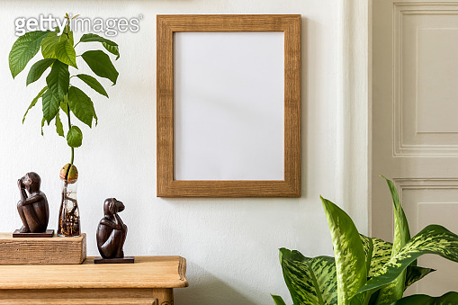 Minimalistic compositon with wooden vintage commode, brown mock up photo frame, avocado plant, plants and elegant personal accessories. Stylish living room. White walls. Template.