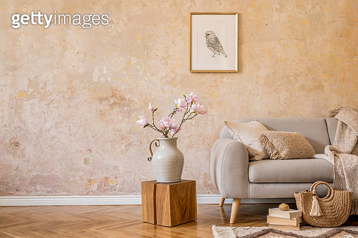 Stylish concept of living room interior with design grey sofa, mock up picture frame, dried flower, wooden cube, books, carpet, woman bag, pillow, plaid and elegant accessories in home decor.