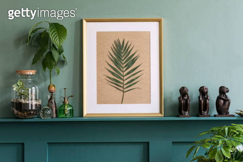 Interior design of living room with mock up photo frame on the green shelf with beautiful plants in different hipster and design pots. Elegant personal accessories. Home gardening. Template.