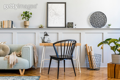 Stylish composition of home office space with sofa, wooden desk, design chair, mock up poster frame, carpet, plants, books, lamp, office supplies and personal accessories in modern home decor.