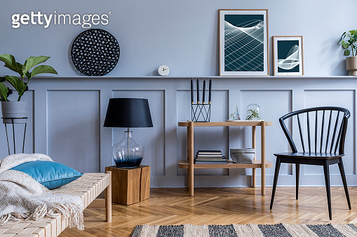 Modern interior of living room with design wooden console, chaise lounge, lamp, plants, mock up poster frame, decoration and elegant personal accessories in stylish home decor.