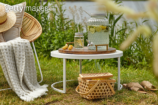 Stylish composition of outdoor garden on the lake with design rattan armchair, coffee table, plaid, pillows, drinks and elegant accessories. Summer chillout mood.