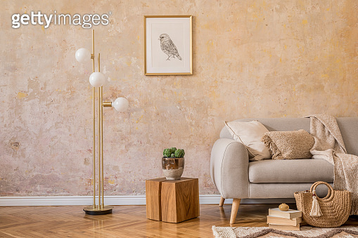 Stylish scandi compostion at living room interior with design gray sofa, wooden coffee table, shelf, cube, carpet, rattan pouf, plants, picture frame, table lamp and elegant accessories in home decor.