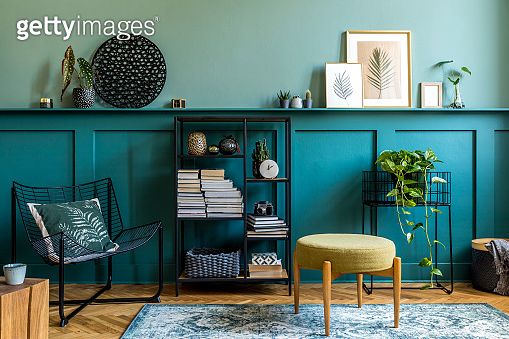 Interior design of living room with design armchair, retro pouf, wooden cube, organizer and elegant personal accessories. Wood panelling with shelf. Modern home decor. Mock up poster frames. Template