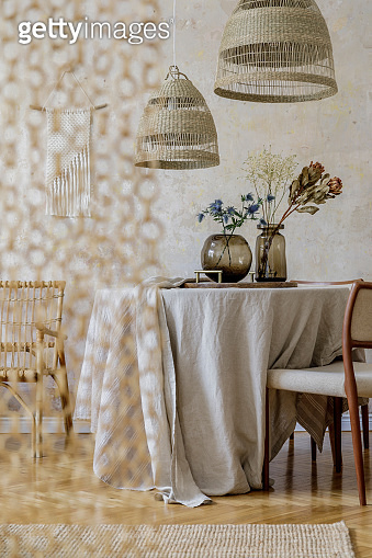 Stylish and elegant dining room interior with diner table, design chairs, rattan pendant lamps, beautiful flowers in vases, furniture, decoration and elegant personal accessories in cozy home decor.