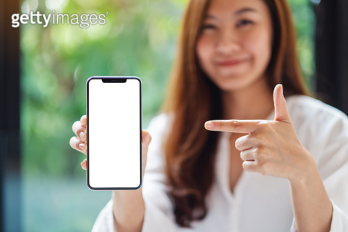 a beautiful asian woman pointing finger at a mobile phone with blank white screen , blurred green nature background