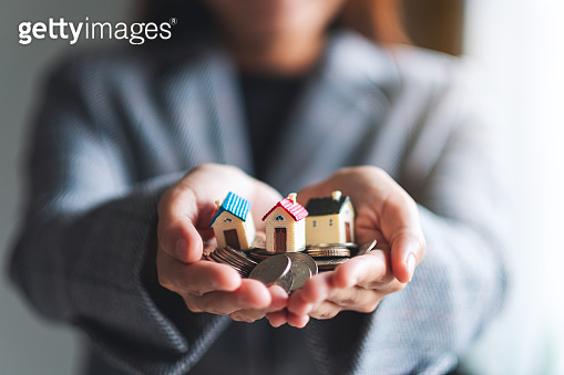 people holding coins and house models in hands