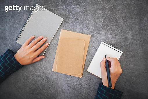 a hand holding a pen and going to write on a blank white notebook