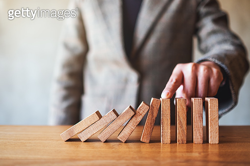 a businesswoman's finger try to stopping falling wooden dominoes blocks for business solution concept