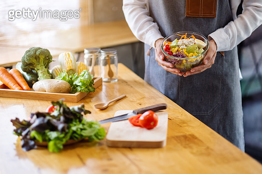 a female chef cooking and holding a bowl of fresh mixed vegetables salad in kitchen
