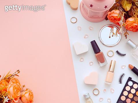 Makeup tools cosmetics, nail polish, sponge, lipstick, eyeliner, false eyelashes, perfume, eyeshadows, puff, rose flowers isolated on white and pink background