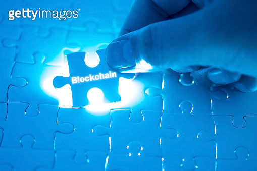Blockchain word on jigsaw puzzle. Businessman hands holding white puzzle business concept. Business, finance, salary, crisis, and development concept. New year planing.