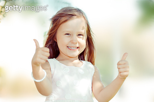 The little girl happy toddler kid showing thumbs up gesture with hands,  outdoors green tree park on background