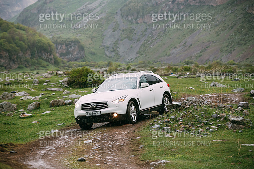 White Infiniti FX30d turbo diesel SUV Car On Off Road In Spring Mountains Landscape In Georgia. Drive And Travel Concept
