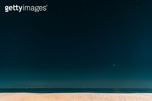 Real Night Sky Stars. Natural Starry Sky In Blue Color Above Sea Seascape Ocean Beach. Background