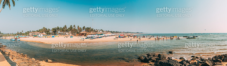 Mapusa, Anjuna, Goa, India. People Visit And Relax On Baga Beach At Sunny Evening Under Blue Sky