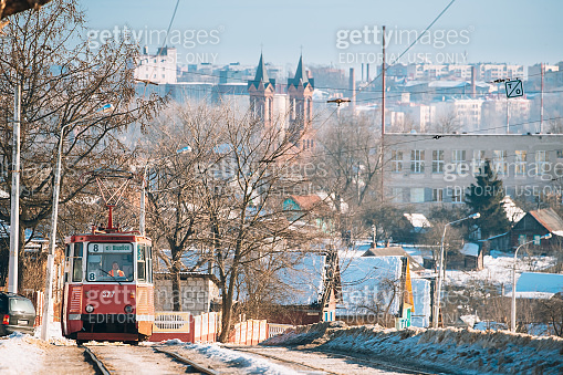 Vitebsk, Belarus. Public Old Retro Tram Of Route Number Eight With Female Woman Driver Moving Near Private Sector And Old Cathedral Of St. Barbara In Winter Day