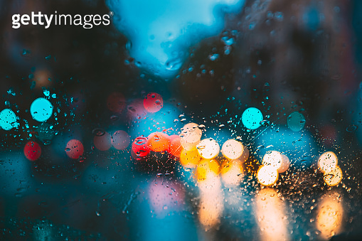 Drops Of Rain Water In Night Or Evening Street Lights On Blue Glass Background. Street Bokeh Lights Out Of Focus. Autumn Abstract Backdrop