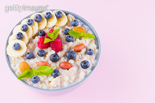 Healthy breakfast. Bowl of oatmeal porridge with fresh blueberries, raspberries, almonds and banana. Clean eating, dieting, detox, vegetarian food concept. Healthy lifestyle concept