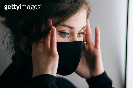 portrait of young beautiful woman in protective black stylish mask with hand with jewelry under her chin, lifestyle 2020 under quarantine and epidemic, fashion disease