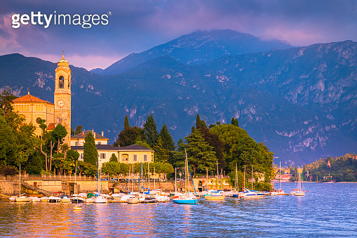 Tremezzina, Tremezzo pier on Lake Como at sunset and Alpine landscape - Lombardy, Italy