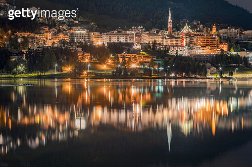 St Moritz illuminated at night and reflection on peaceful lake, Engadine – Switzerland