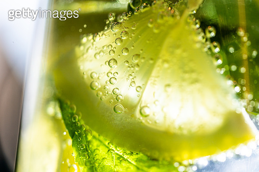 Close-up shot to lemon slice and mint in mineral water