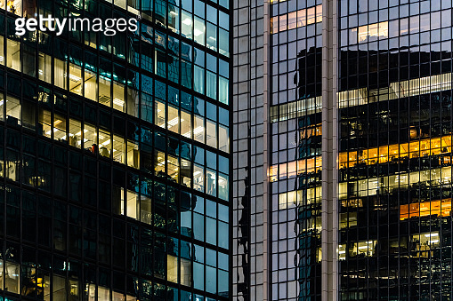 Workers working late. Office windows by night